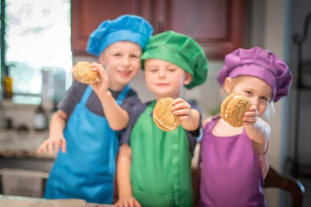 kids wearing aprons and bakers hats holding ice cream sandwiches in their hands.