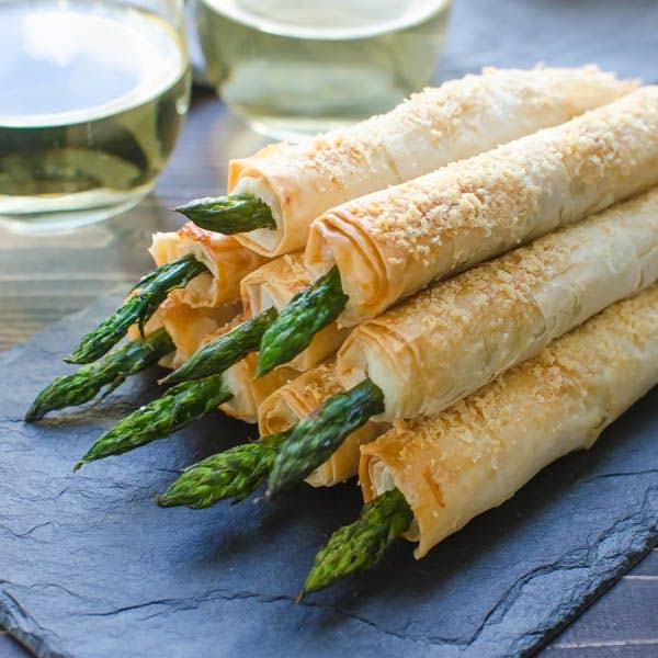 parmesan asparagus spears wrapped in phyllo dough stacked for a party