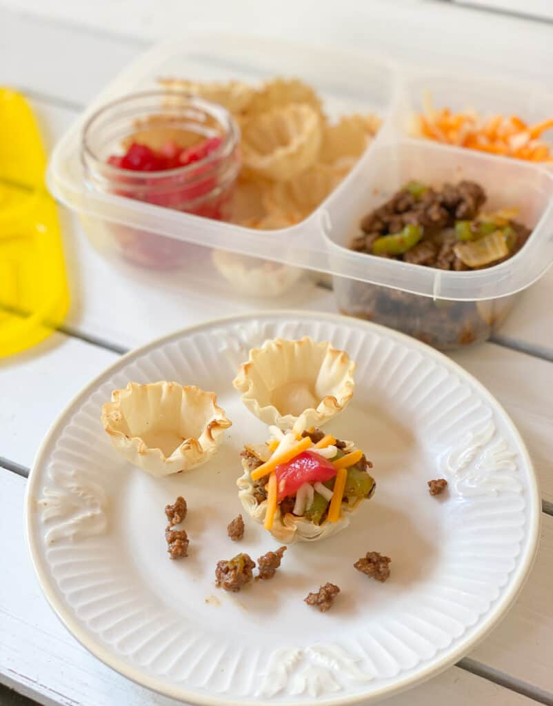 phyllo cups filled with ground meat tomatoes and cheese on a plate