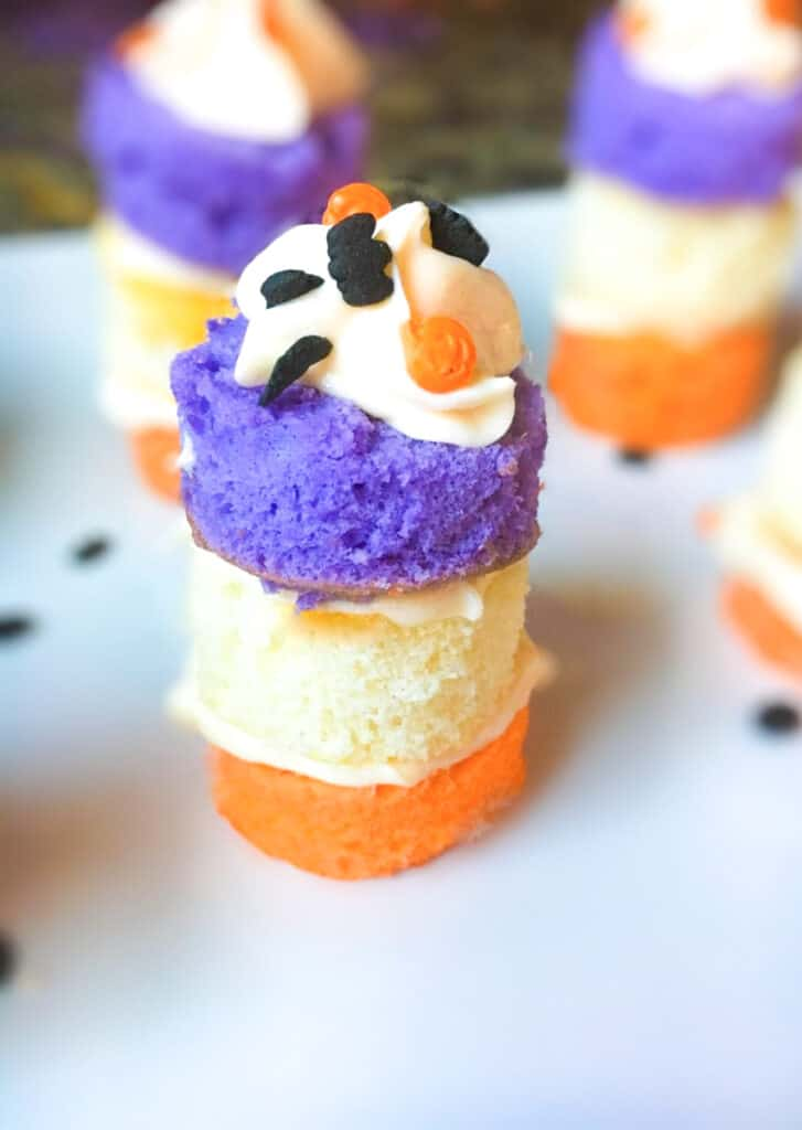 layers of orange, purple and white cake filled with icing and Halloween sprinkles on top