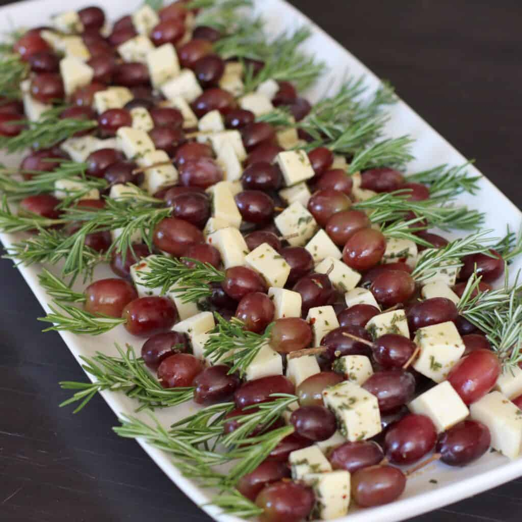 grapes and fontina skewered with rosemary on a plate.