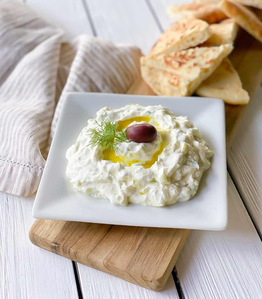 greek yogurt dip with pita bread on cutting board