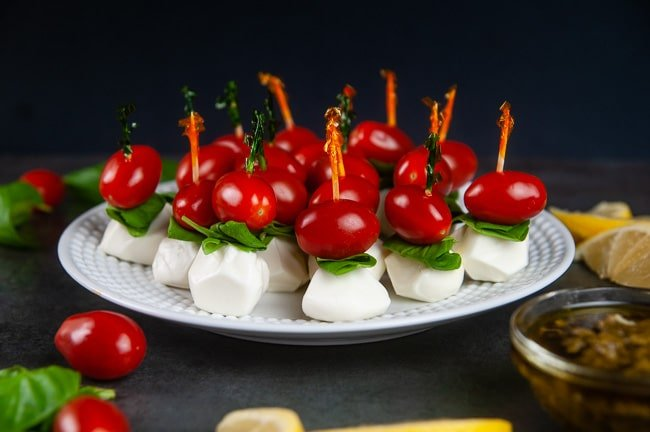 mini caprese appetizer skewers on a white plate.