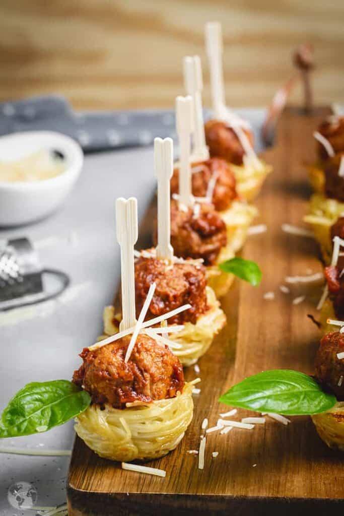 mini spaghetti and meatball skewers on a wooden cutting board.