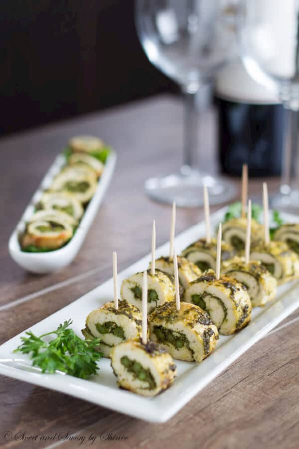 pesto chicken skewers on a white plate served with toothpick skewers.