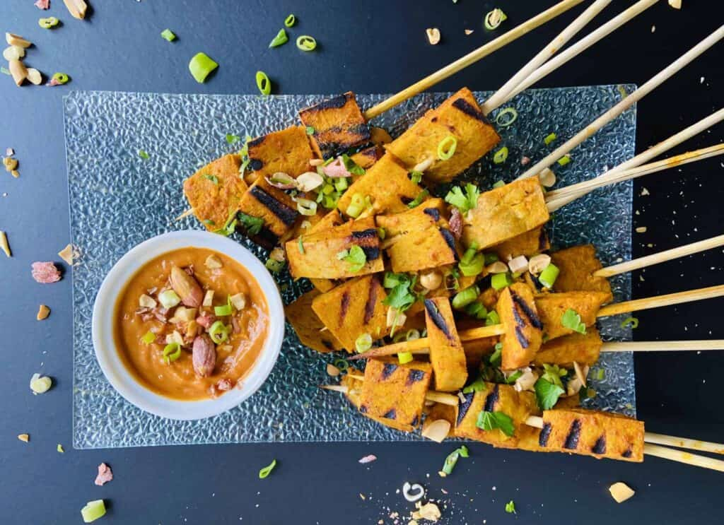 vegan satay skewered grilled and skewered on long wooden kabobs on a plate.