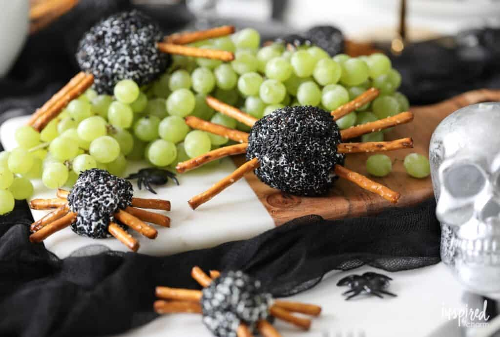 cheeseballs coated in sesame seeds with pretzel sticks as legs to look like spiders
