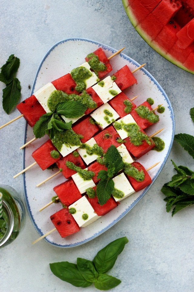 mini watermelon skewer appetizers on a plate with feta cheese and mint.