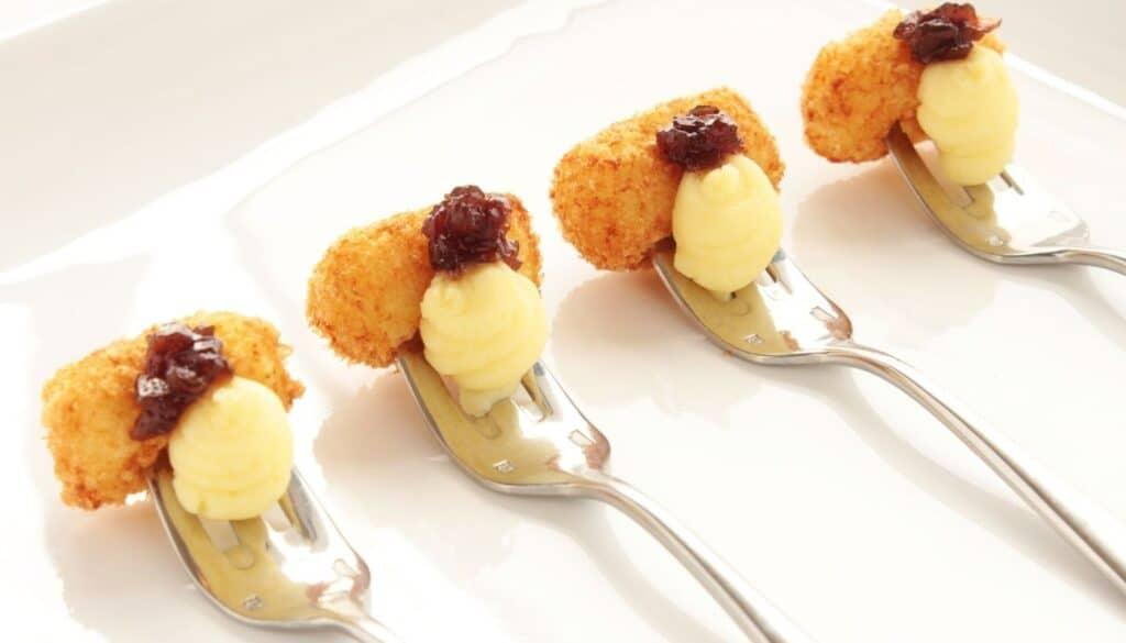 Amuse bouche appetizer served on forks on a serving platter.