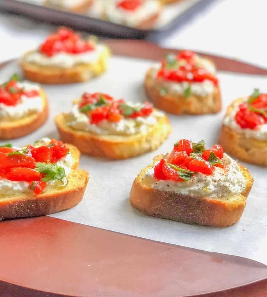 crostini appetizer on a plate topped with ricotta cheese, basil and roasted red peppers