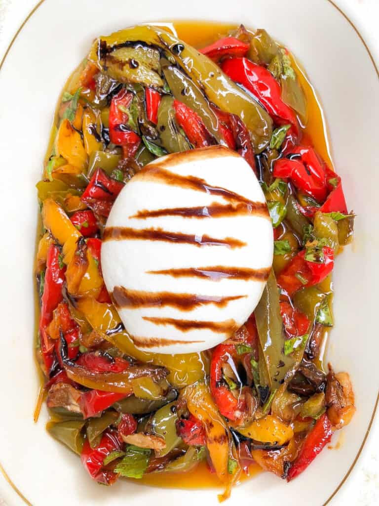 Italian burrata cheese served over top of roasted peppers and garlic in a bowl