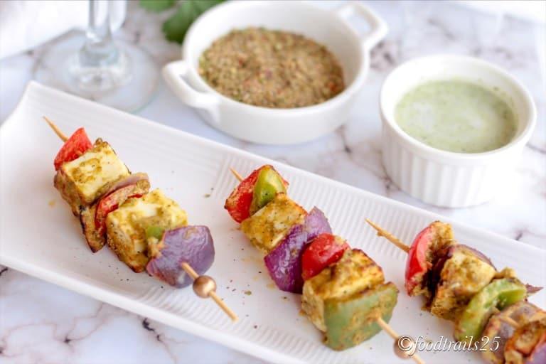 paneer tikka chicken skewers with veggies on a plate.