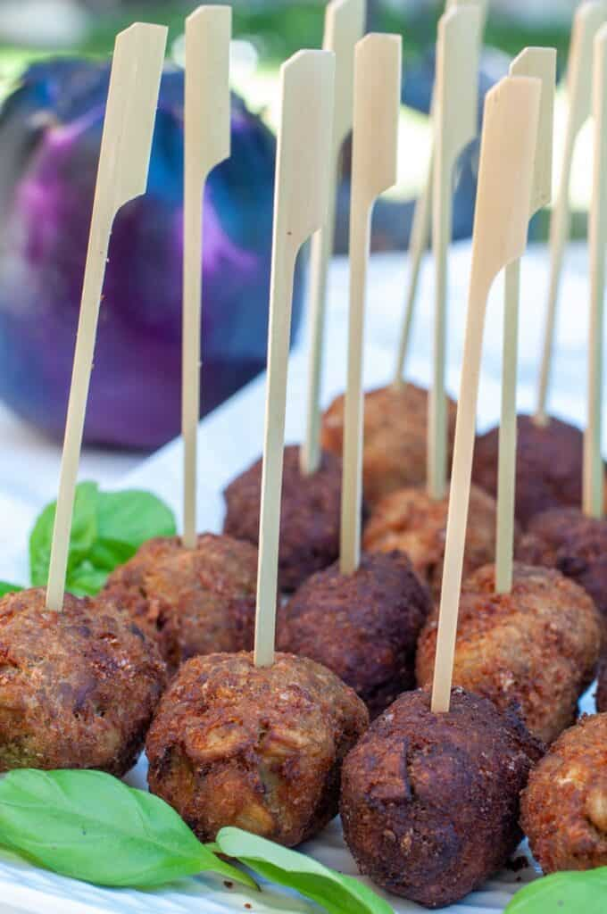 fried eggplant balls skewered and served on a plate.