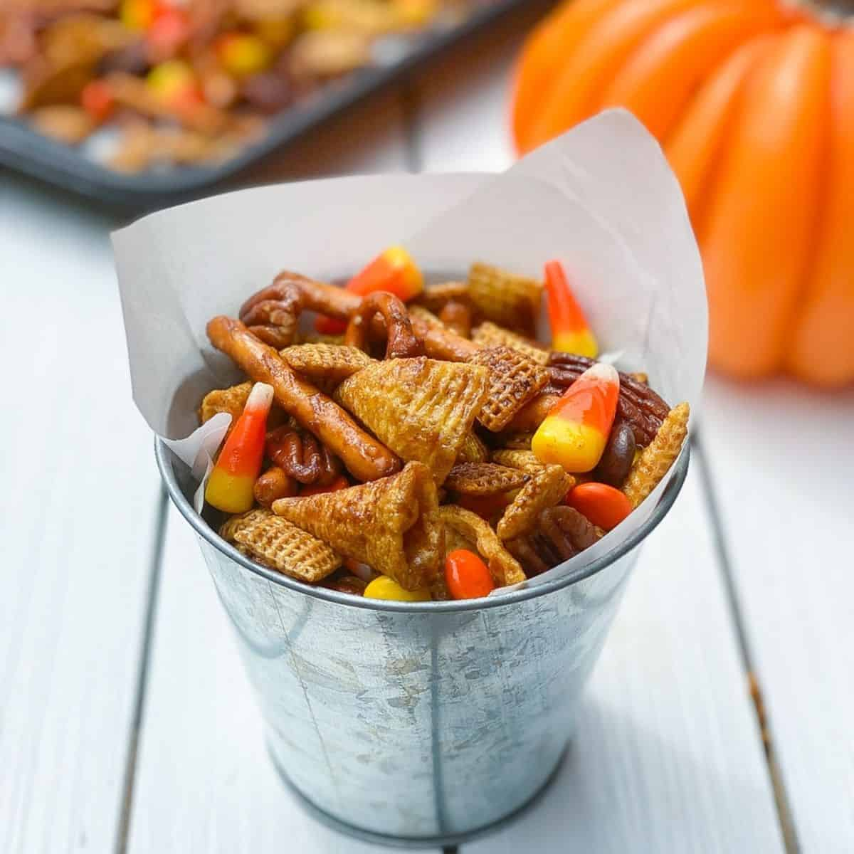 Halloween spiced Chex mix in a metal tin with candy corn.