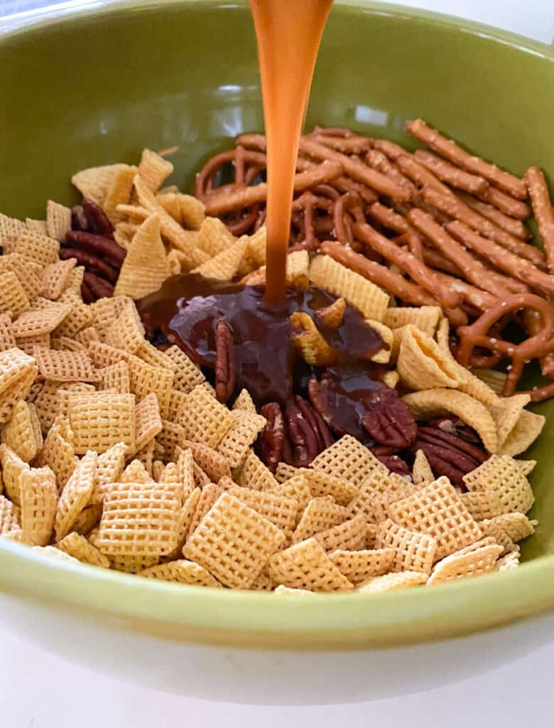 chex mix in a bowl being poured with a brown sugar pumpkin spice glaze