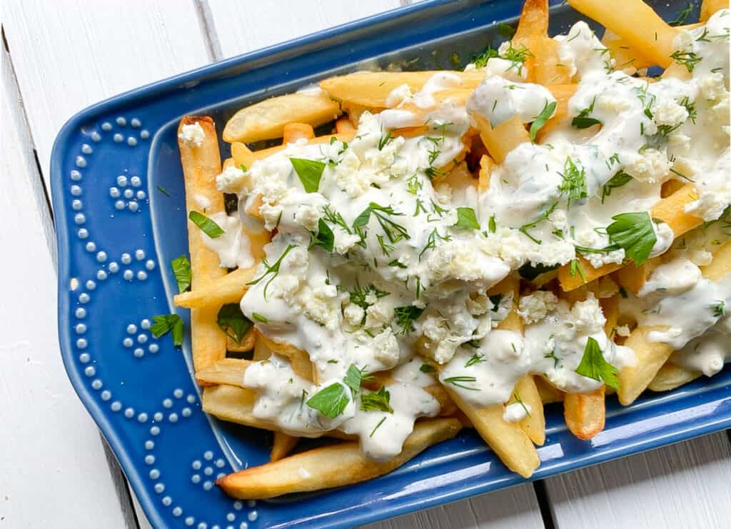 overhead shot of Greek feta cheese fries on a blue plate.
