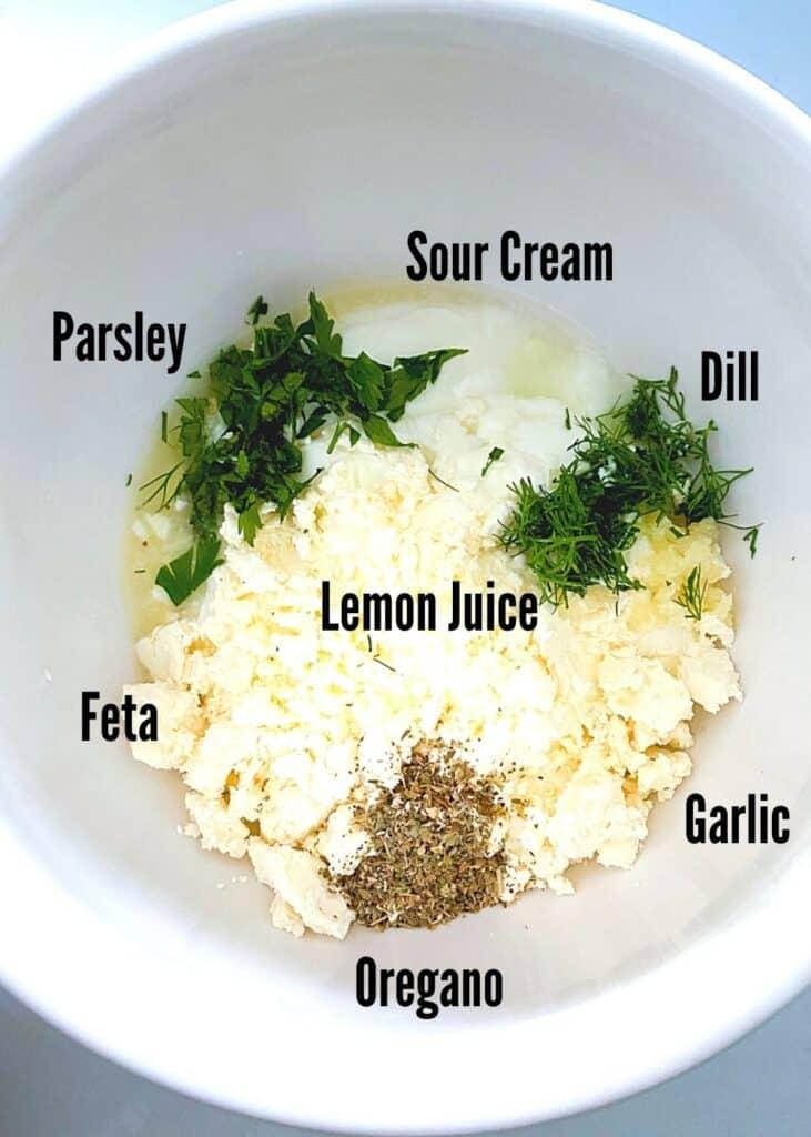 Greek feta fries sauce ingredients in a white bowl.