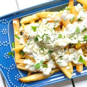 Greek french fries covered with feta cheese and yogurt sauce on a blue plate.