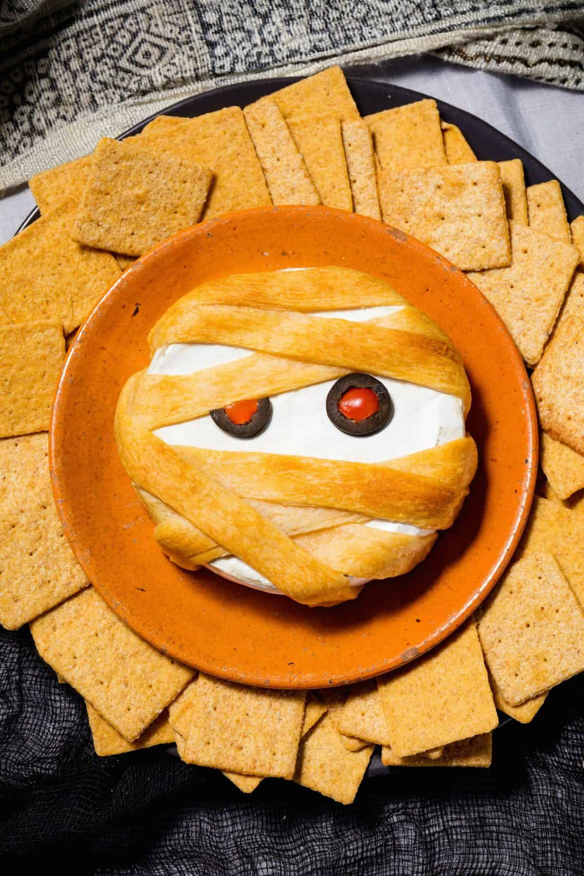 brie cheese appetizer wrapped in puff pastry dough to look like  a mummy.