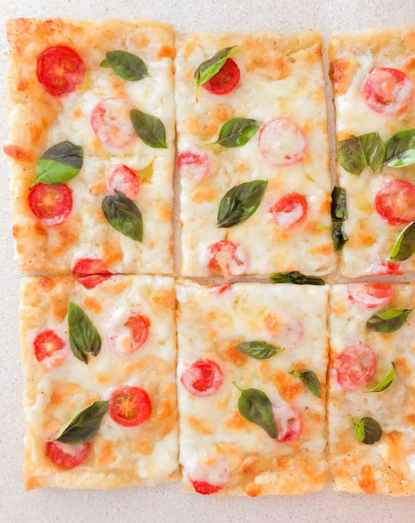 overhead shot of puff pastry pizza with mozzarella cheese and tomatoes