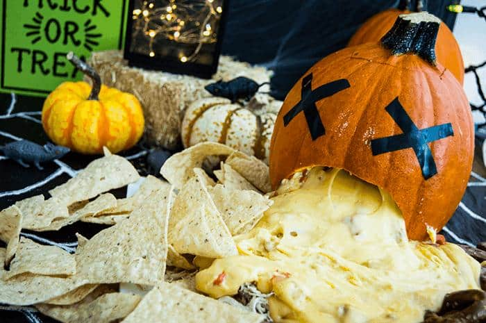 large pumpkin with cheese spilling out of the mouth onto nachos