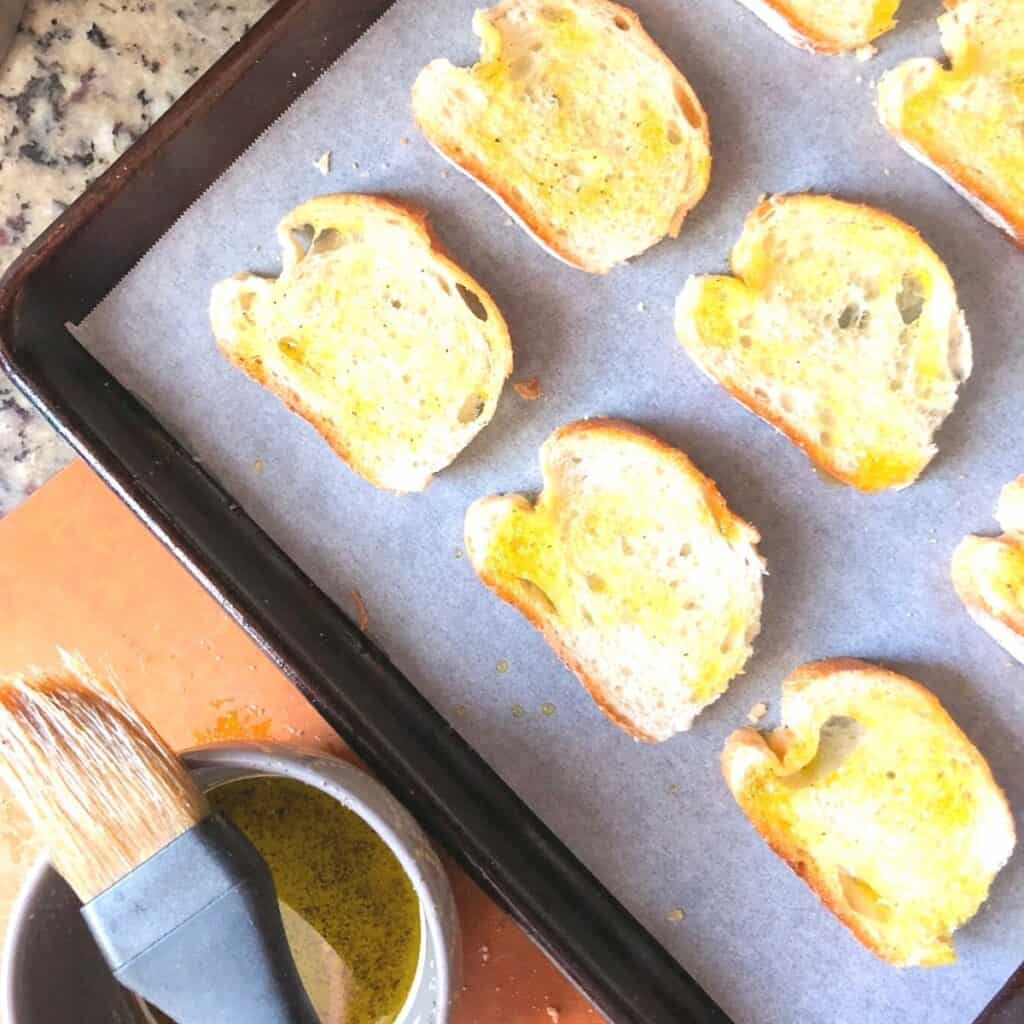 brushing crostini with extra virgin olive oil