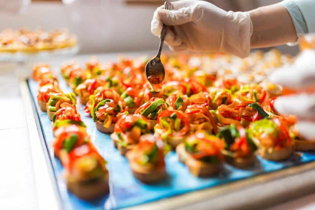 caterer spooning glaze over top of canapes before serving
