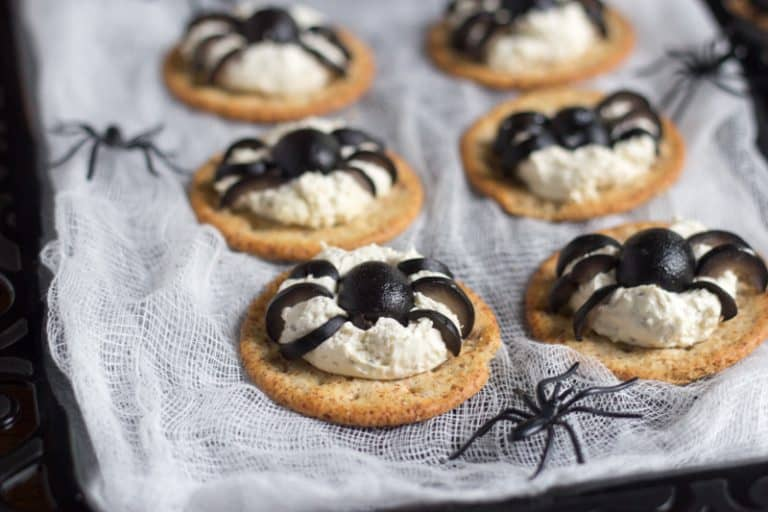 crackers with cheese are topped with olives to resemble spiders