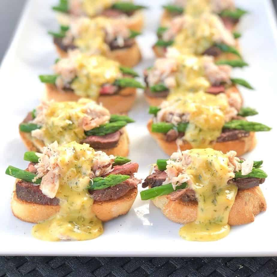 steak and crab over top of crostini with sauce on a platter.