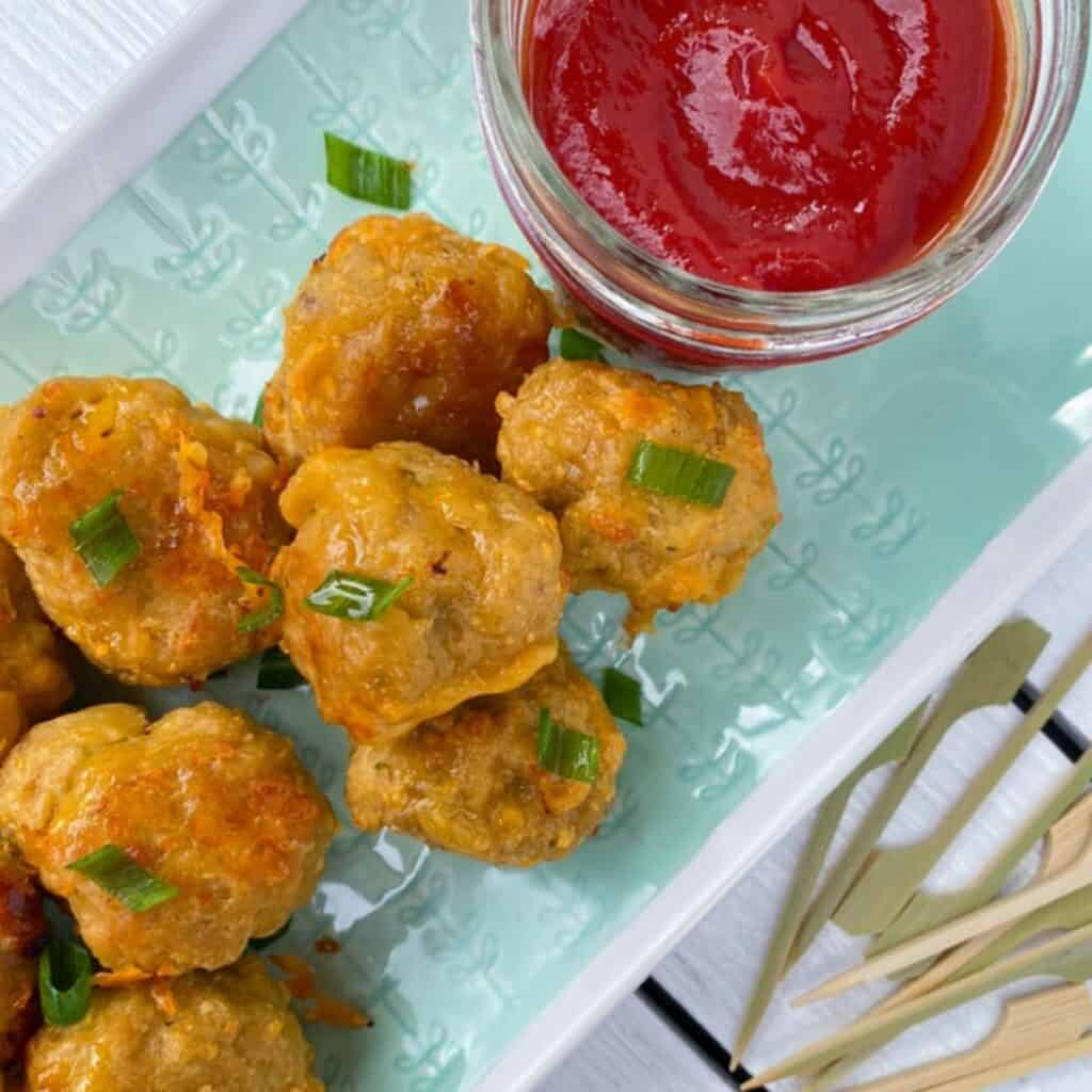 sausage balls on a plate with toothpick skewers and dipping sauce