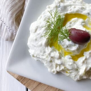 greek tzatziki on a plate with an olive and olive oil.