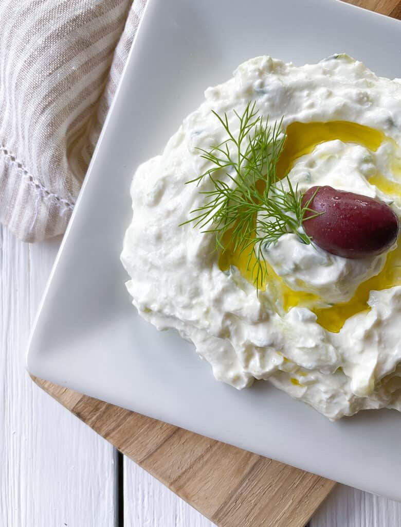 overhead shot of Greek tzatziki dip on a plate with an olive.