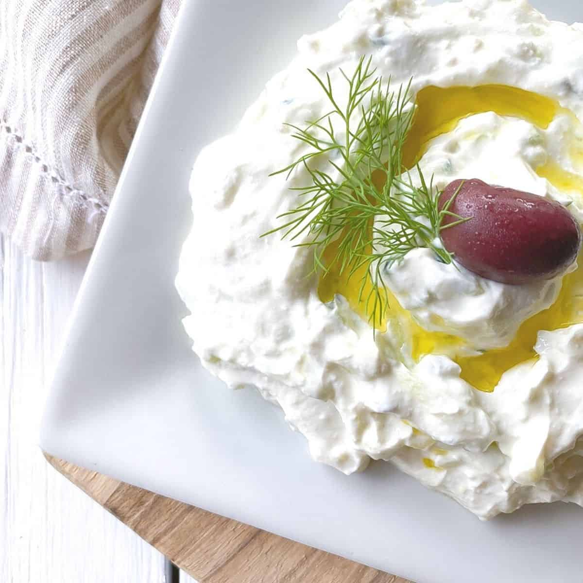 greek yogurt tzatziki dip on a plate with olive oil and olive