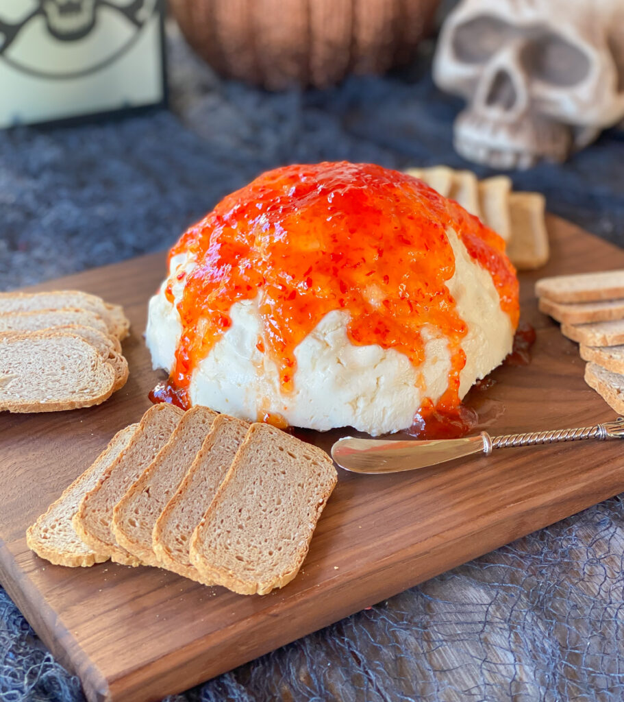 brain mold dip on board with jam over top and crackers