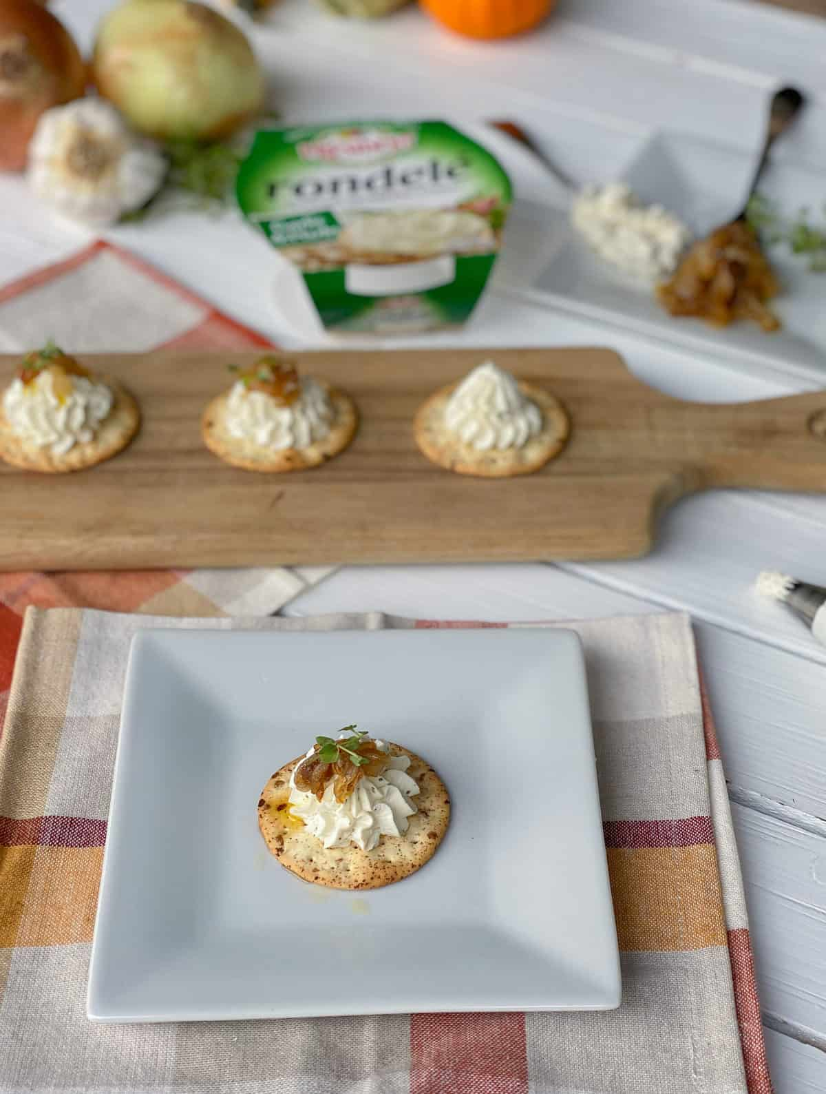 canape crackers on plate with onions and cheese.