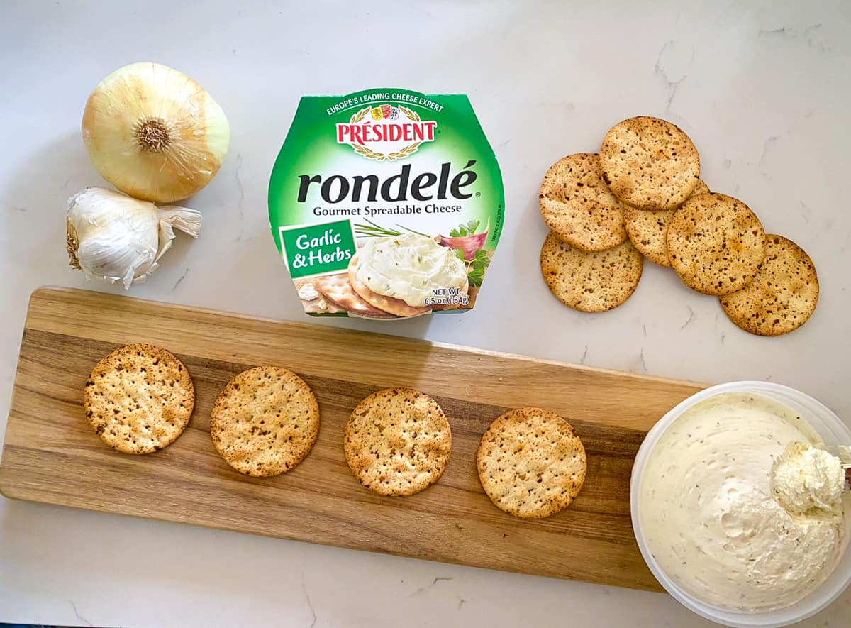 rondele cheese spread with canape crackers on cutting board.
