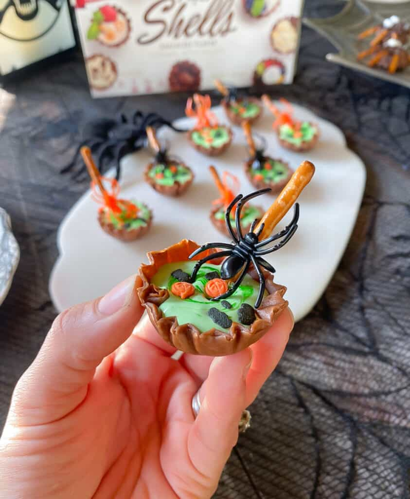 holding up one chocolate phyllo shell with spider and pretzel stick