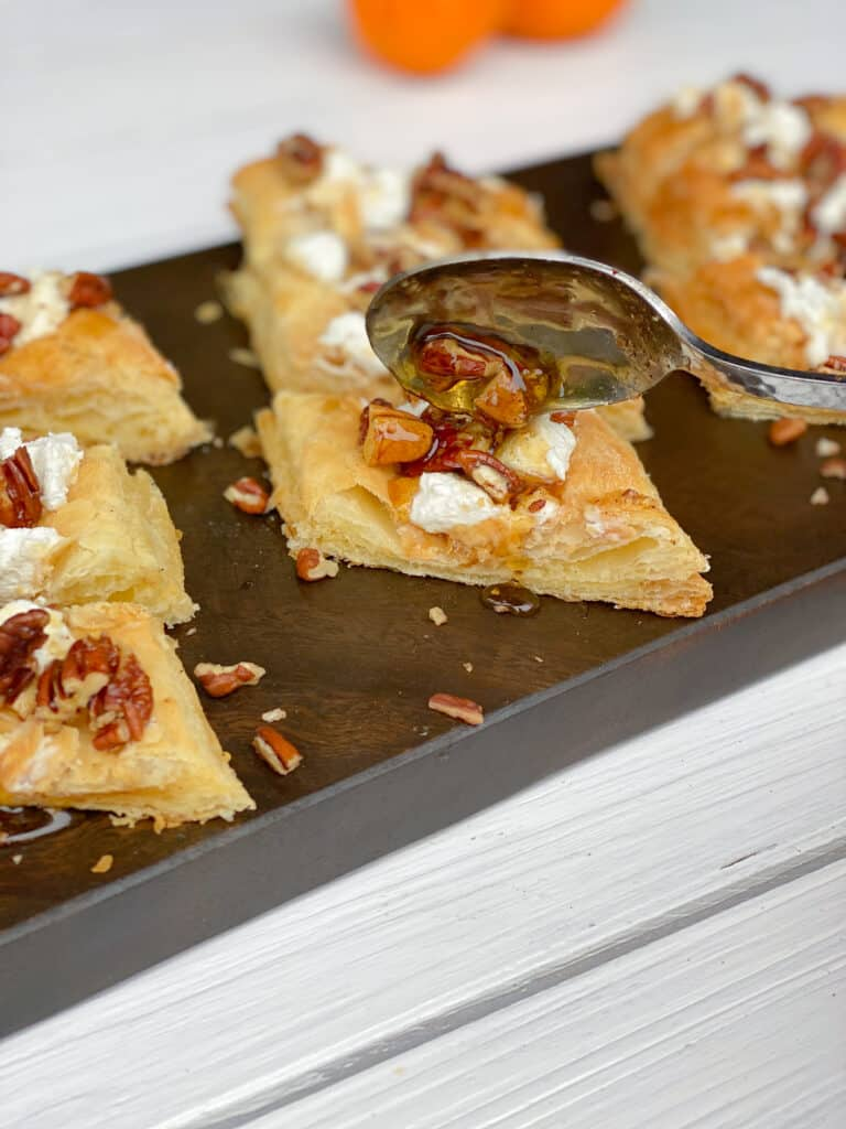 spooning maple pecan mixture over top of goat cheese puff pastry