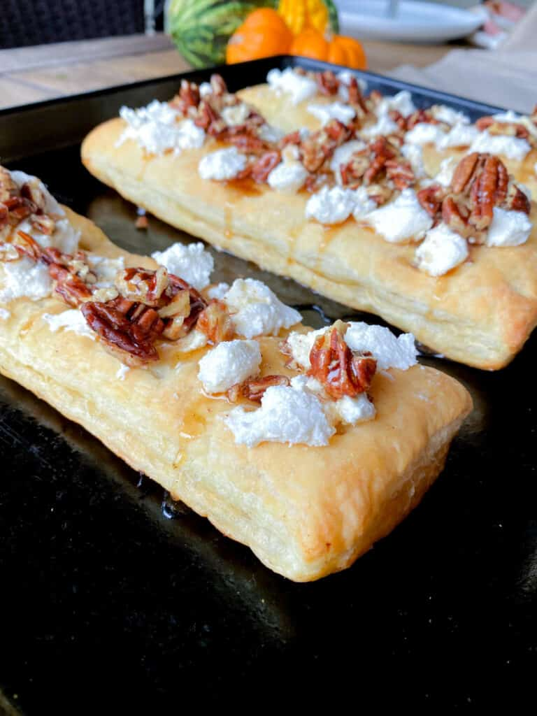 puff pastry on a baking sheet topped with goat cheese and spiced pecans