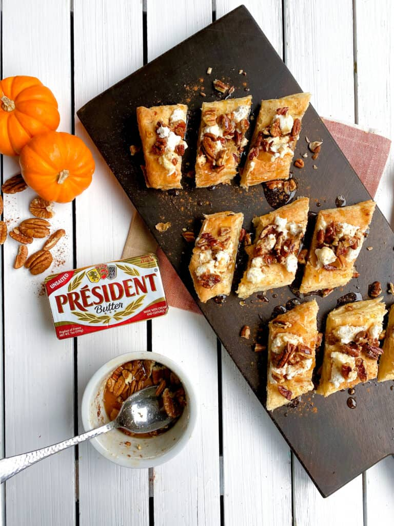 overhead shot of puff pastry dessert on cutting board with pecans and goat cheese