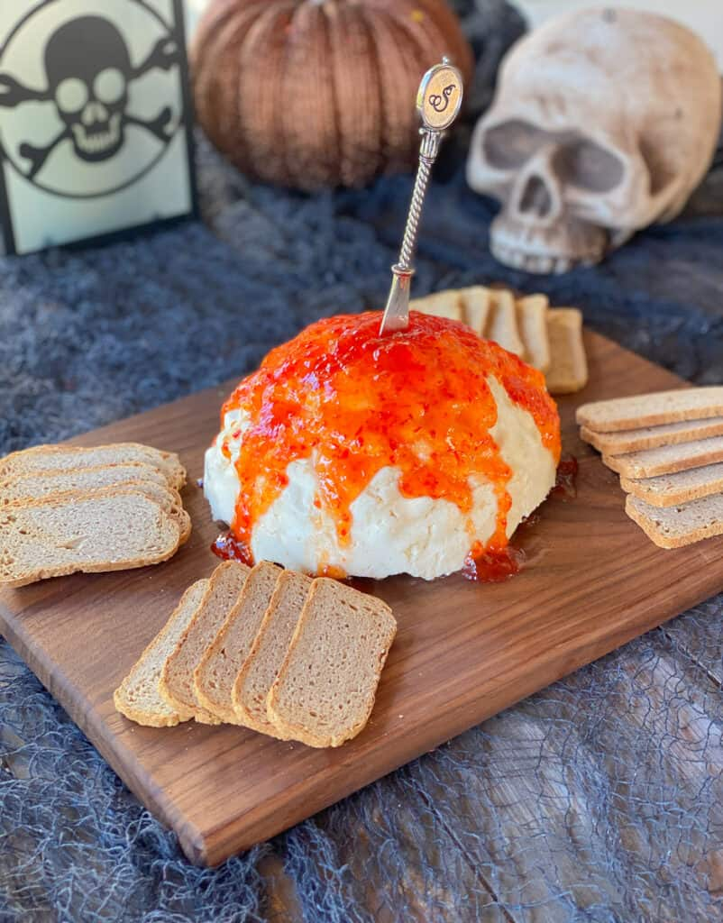 cream cheese brain dip on cutting board with crackers around it