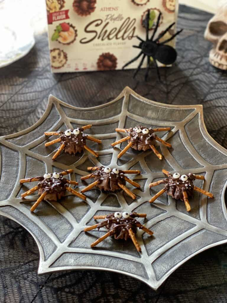 chocolate phyllo shells with pretzels for legs and drizzled with chocolate and sea salt on spooky web plate