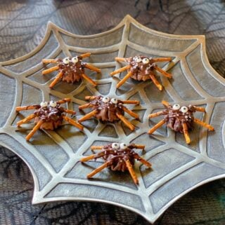 chocolate pretzel spiders on a spider web plate