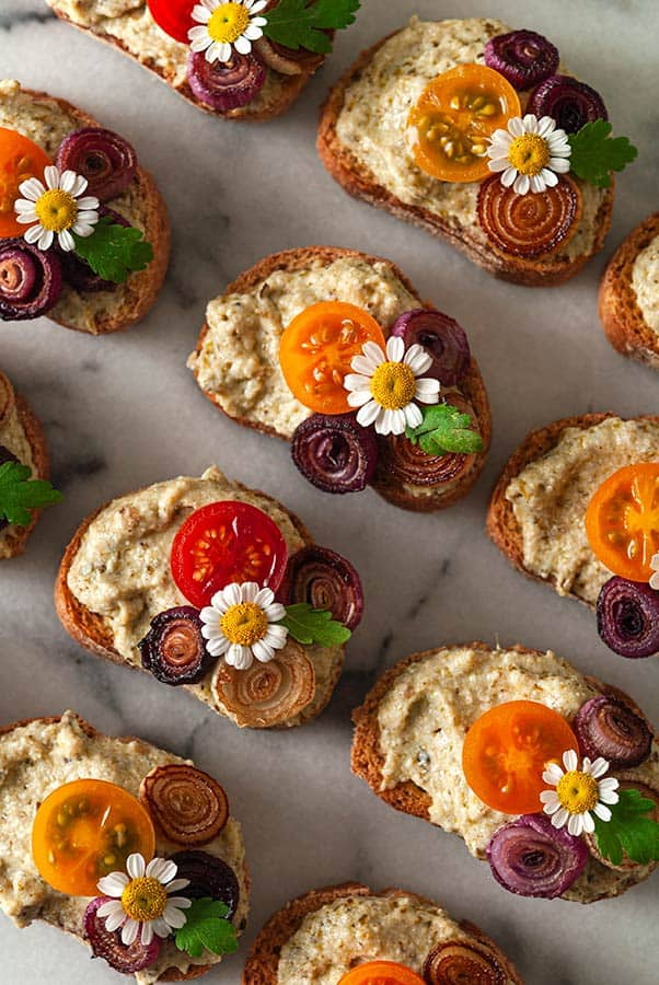 overhead shot of pesto ricotta crostini with colorful toppings, onion and flowers.