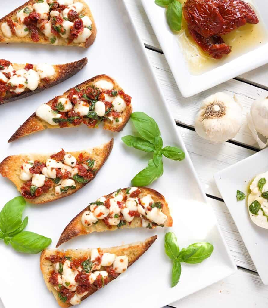 bruschetta caprese with sun dried tomatoes on plate with basil and garlic