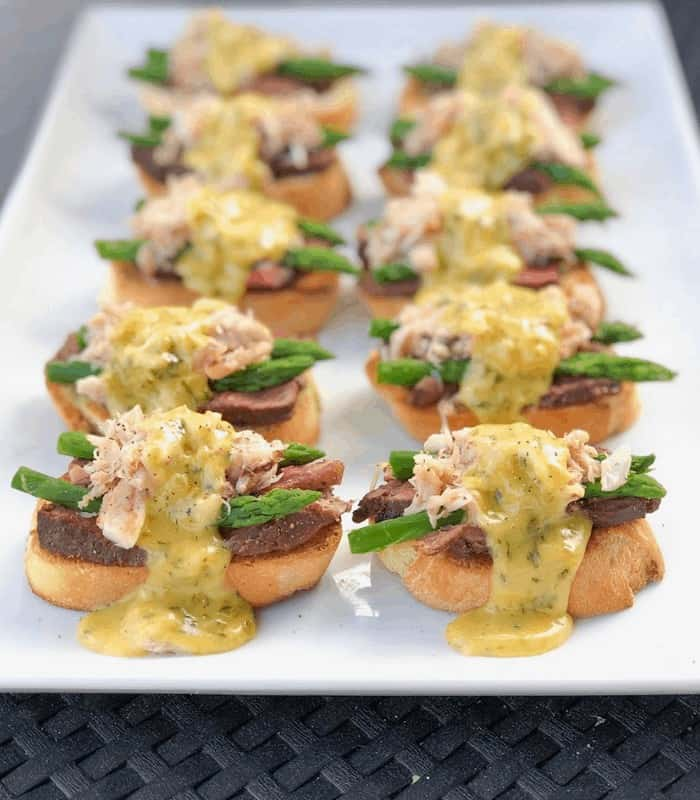crostini with steak, crab, asparagus and sauce on plate.
