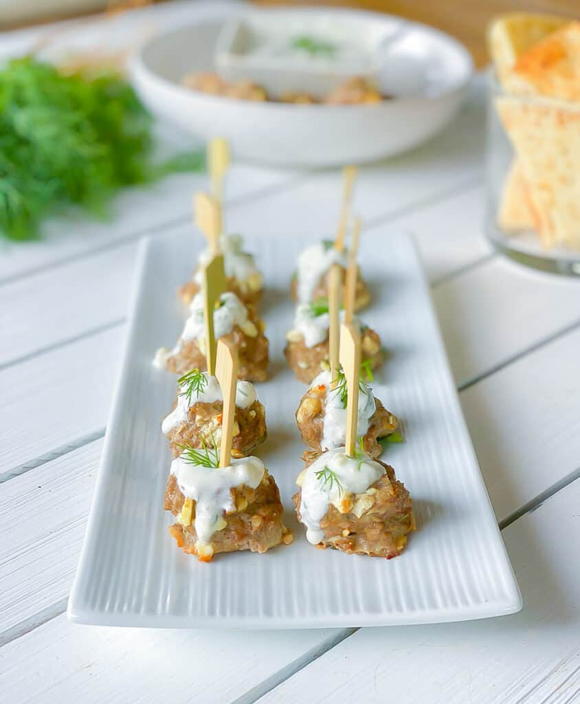 lamb meatball hors d'oeuvres on a serving plate with yogurt sauce.