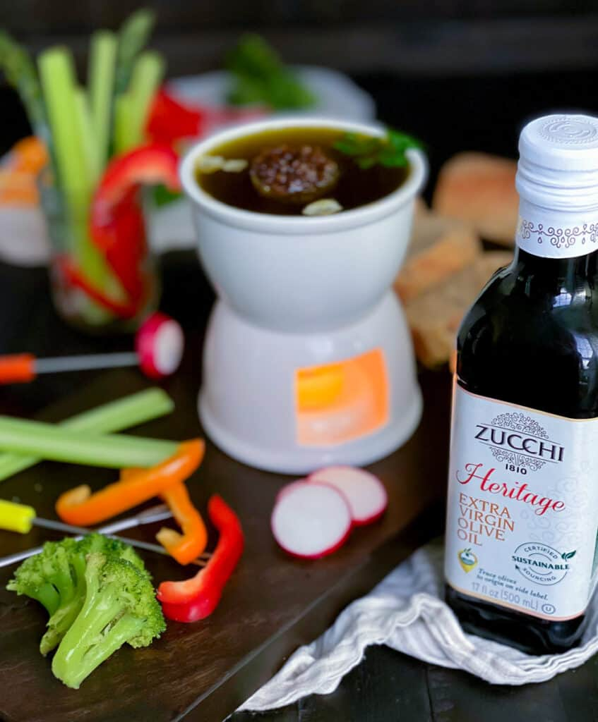 bagna cauda dip with a bottle of zucchi olive oil next to vegetables