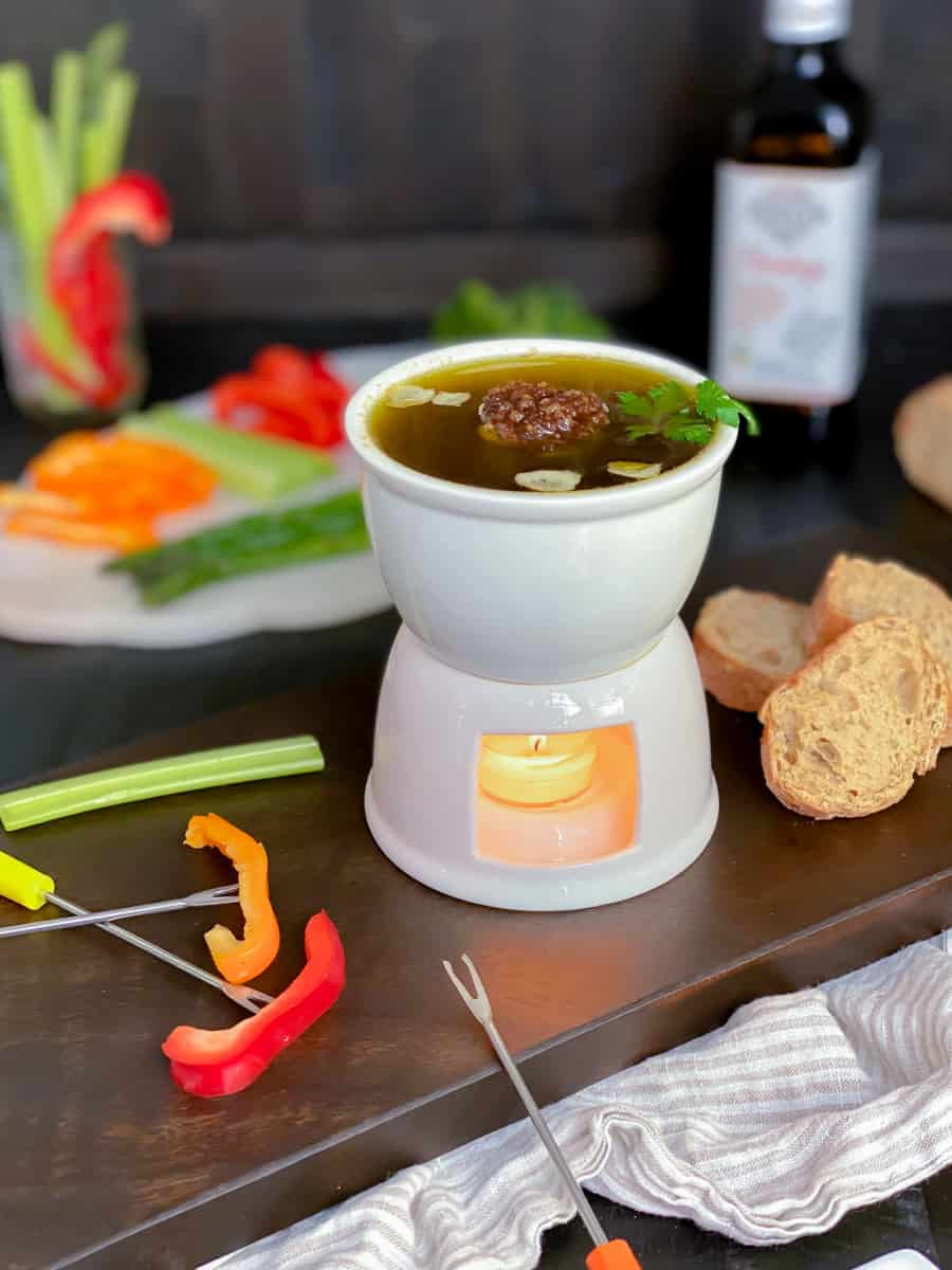 bagna cauda in a fondue pot with a variety of vegetables to dip into on a cutting board.