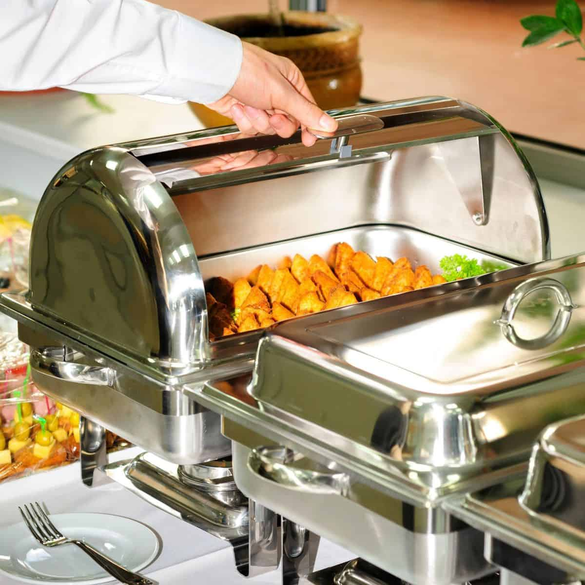 hand opening chafing dish at buffet table.